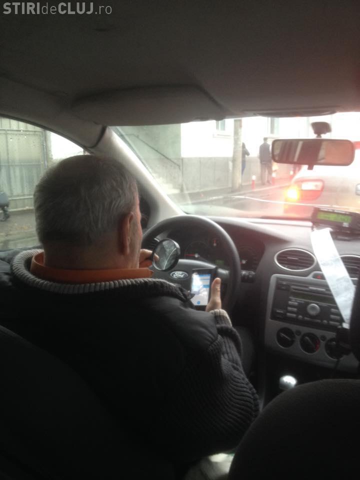Acest șofer de taxi citește mesaje în timp ce conduce! Șocant e altceva - FOTO