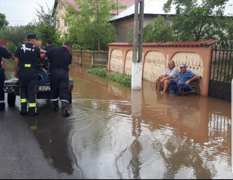 IMAGINEA ZILEI e din Teleorman. Doi localnici stau pe bancă în timp ce pompierii scot apa din comună