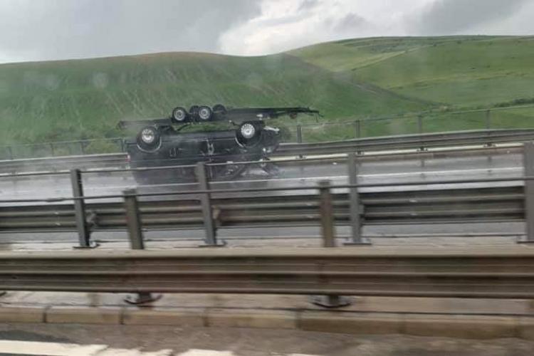 Imagini demne de cascadorii râsului! Platforma încărcată cu o mașină, răsturnată complet pe autostrada A3 FOTO