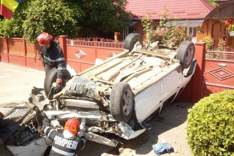 Accident pe drumul Cluj-Gherla. Un șofer s-a răsturnat cu mașina în fața unei porți FOTO