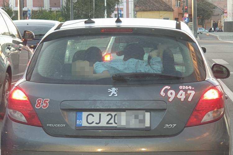 Părinte inconștient la Cluj! Își lasă copilul să stea deasupra porbagajului, sub luneta mașinii - FOTO