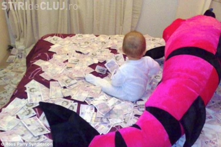 Fotografia care a SCANDALIZAT Anglia! Un bebelus roman se tavaleste in bancnote de 20 de lire furate din bancomate