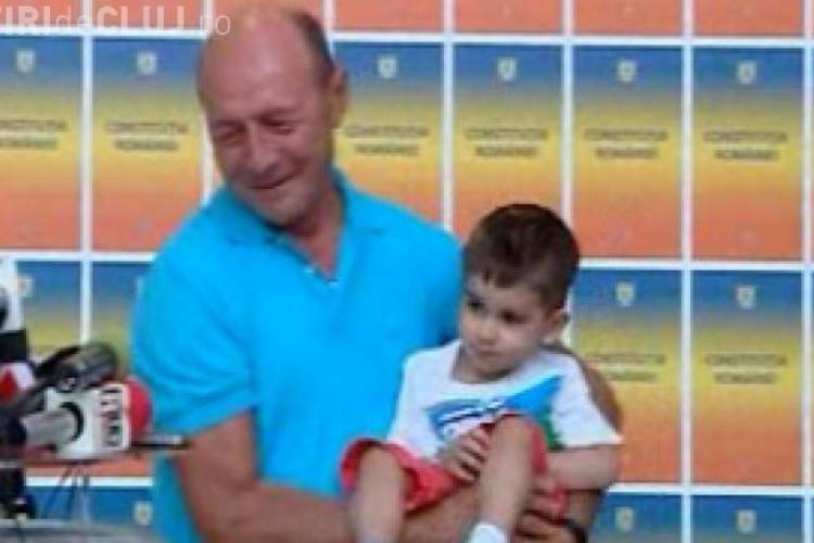 Băsescu a luat un copil în brațe la conferinţa de presă