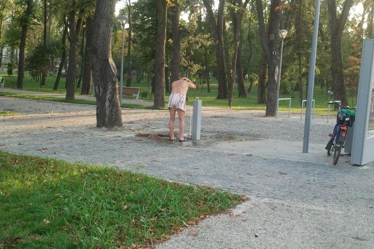Un bărbat aproape dezbrăcat, făcea baie la o cișmea din Parcul Central - FOTO