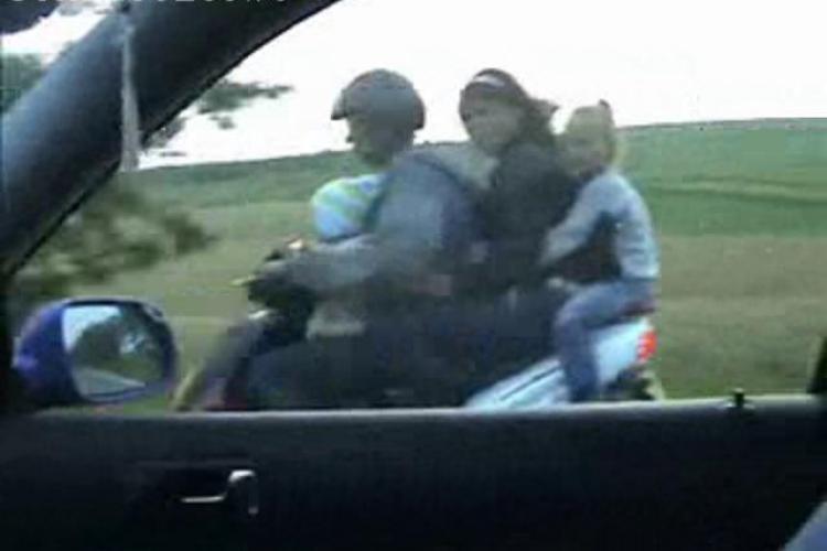 VIDEO - Patru pe un scuter pe un Drum National. Soferul inconstient are doi copii langa el si trece pe rosu