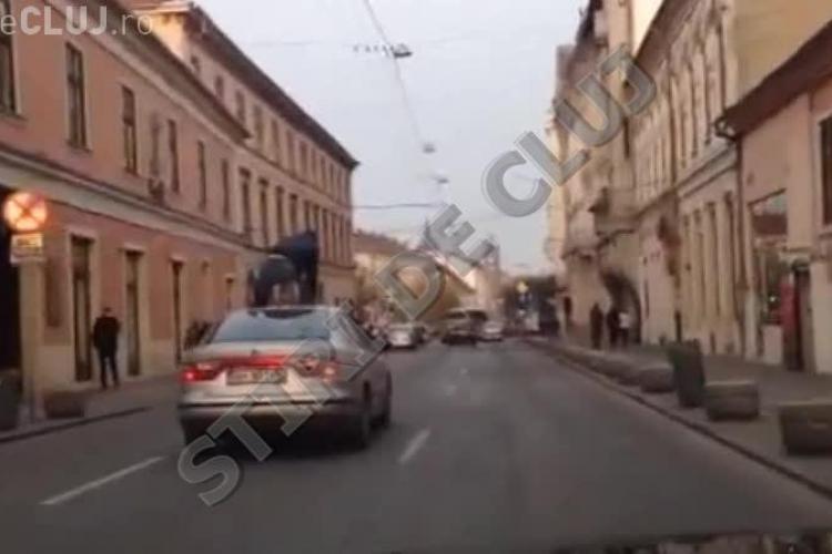 Tânăr CĂLARE pe capota unei mașini prin centrul Clujului! Imagini INCREDIBILE - VIDEO